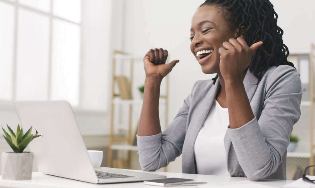 A Female business leader celebrating a success via zoom.